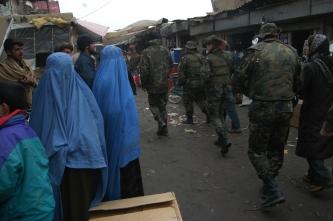 12 Mujeres y hombres observan el paso de militares españoles en Kabul